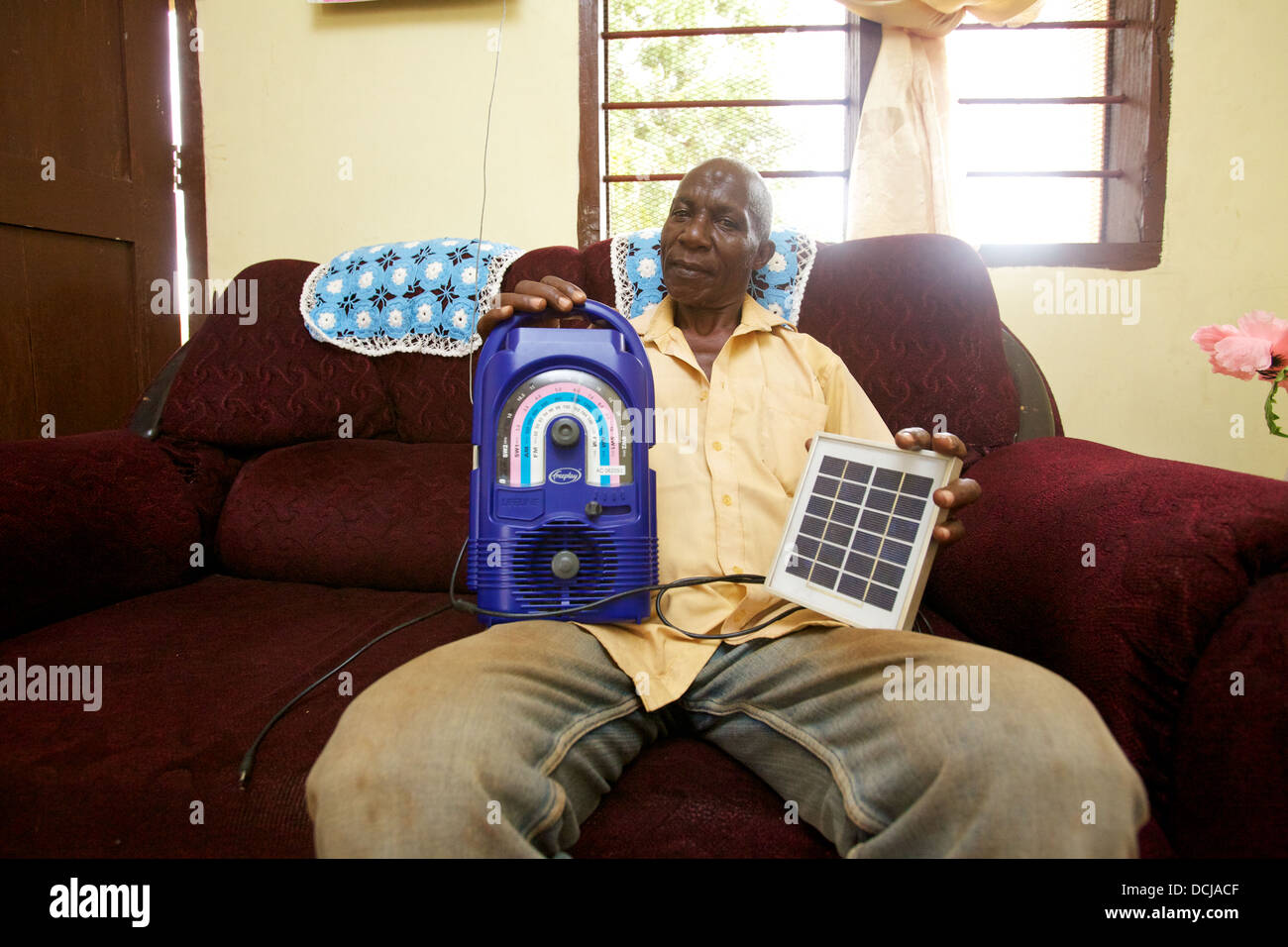 Tanzanian man at home holding wind-up radio and a portable solar panel, Miono Region, Tanzania. - Stock Image