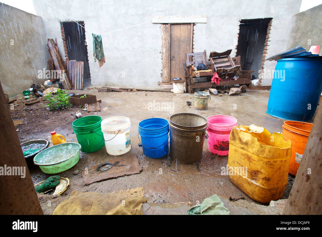 Buckets laid out in a courtyard to collect rainwater, Tanzania, Africa - Stock Image