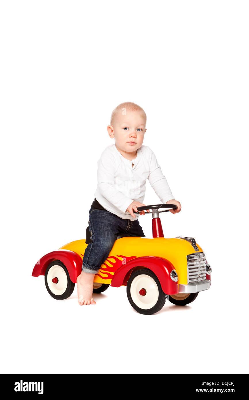 Boy riding his toycar - Stock Image