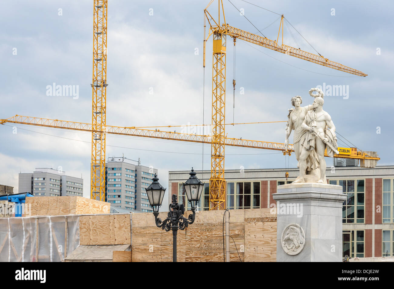 Construction site with tower cranes behind a historic statue and historical lighted street lamps - Berlin Germany Stock Photo
