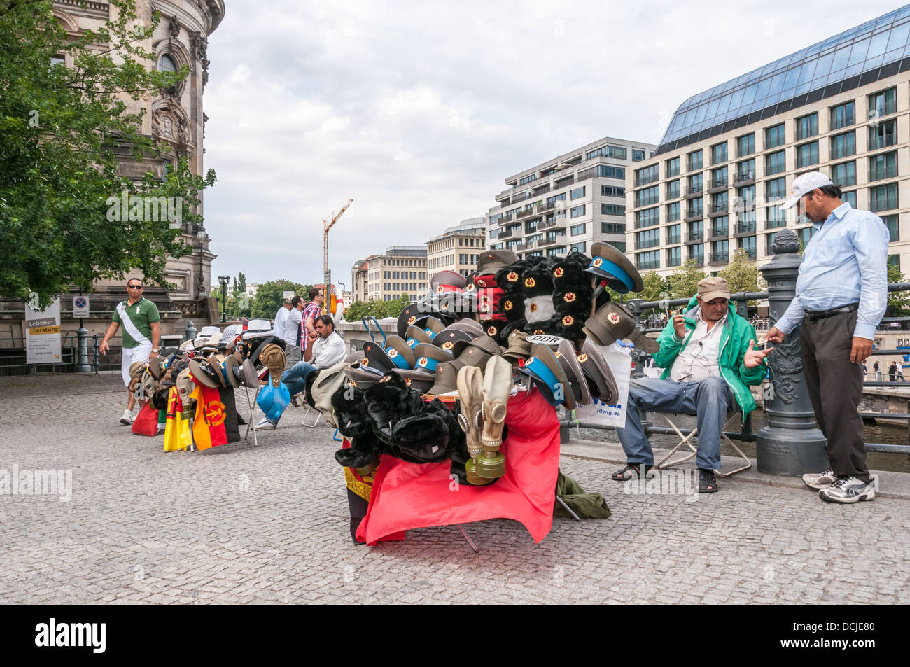 Middle Eastern men, street vendors, selling military memorabilia, visored caps, flags, at the Berlin Catherdral Stock Photo