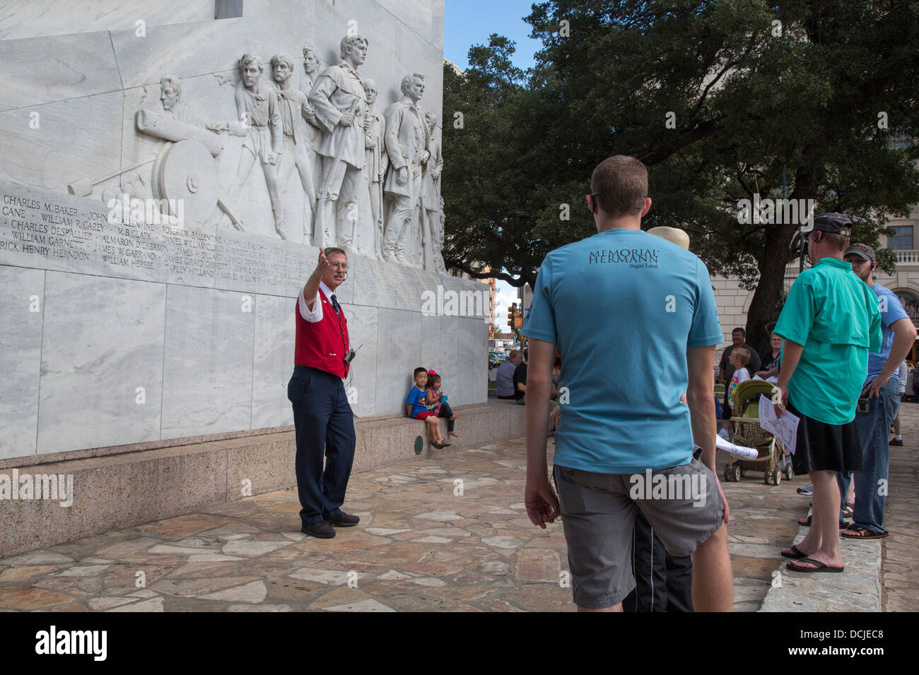 A guide talks to tourists about the Alamo - Stock Image