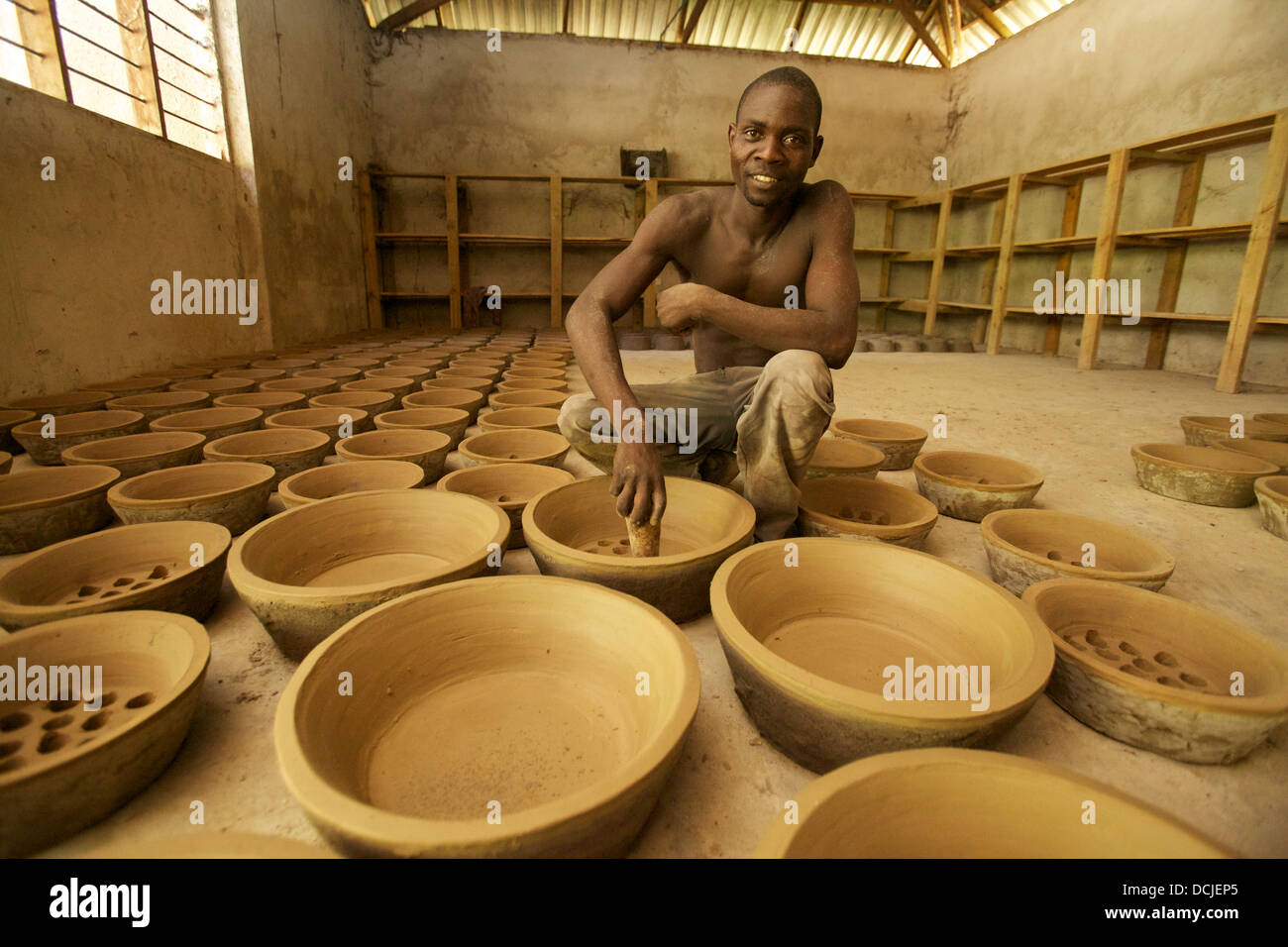 Tanzanian potter punching holes in clay liners used for the production of african cooking stoves, Tanzania. - Stock Image