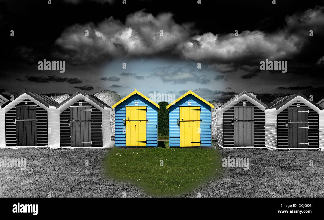 A surreal monochrome image with some colour of beach huts. - Stock Image