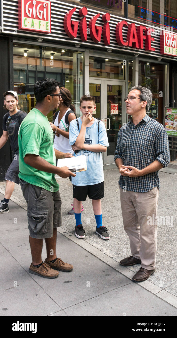sincere Greenpeace volunteer spreading message of environmental issues to concerned pedestrians on East 34th street - Stock Image