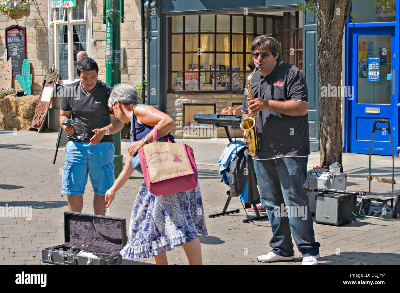 Landscape of some street entertainers in Buxton town centre, in the sunshine, during the summer, UK. - Stock Image