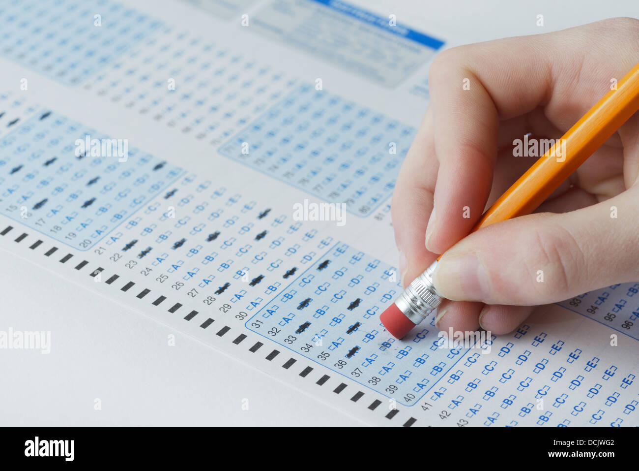 Optical scan answer sheet for a school exam with student erasing answer - Stock Image