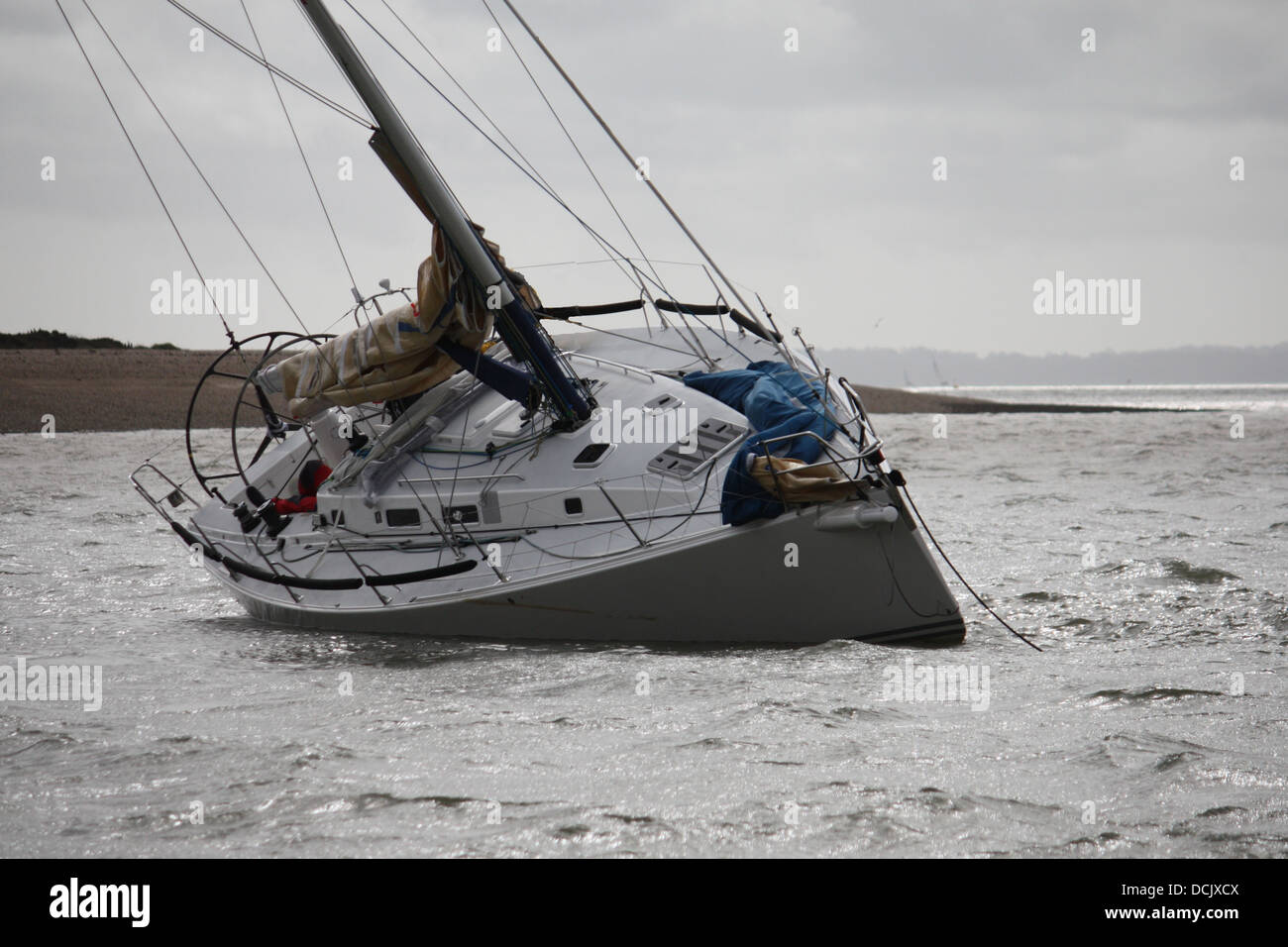 yacht heeling due to being aground at the entrance to hamble river in the solent - Stock Image