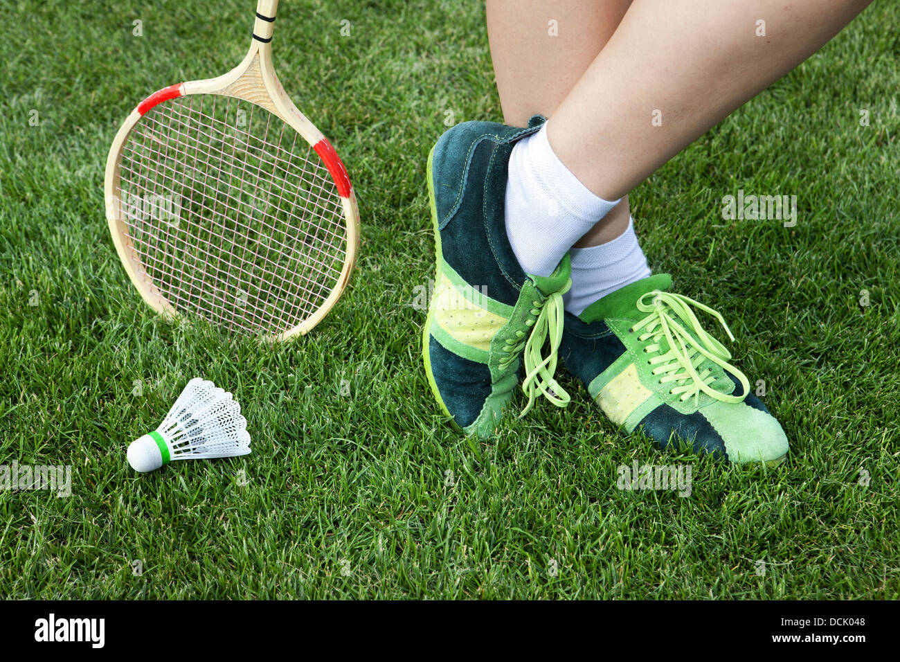 foot of woman who plays badminton on grass - Stock Image