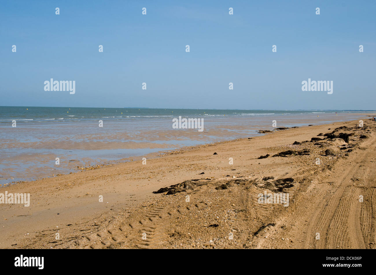 The deserted sandy beach at Notre Dame-de-Monts in the Vendée area of France. Pools of water are left as the - Stock Image