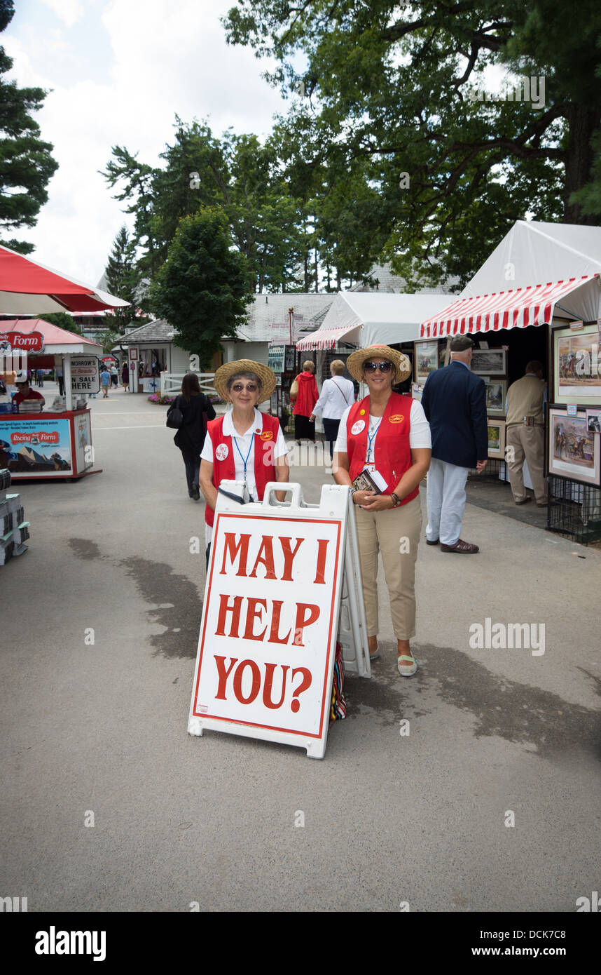 Two friendly women are ready to help visitors at the  entrance to the Saratoga Raceway in Saratoga, New York. - Stock Image