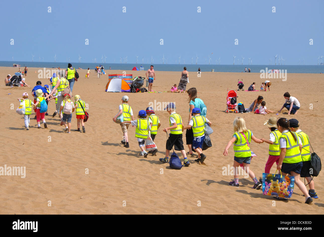 group of school children walking on the beach, Skegness, Lincolnshire, England, UK - Stock Image