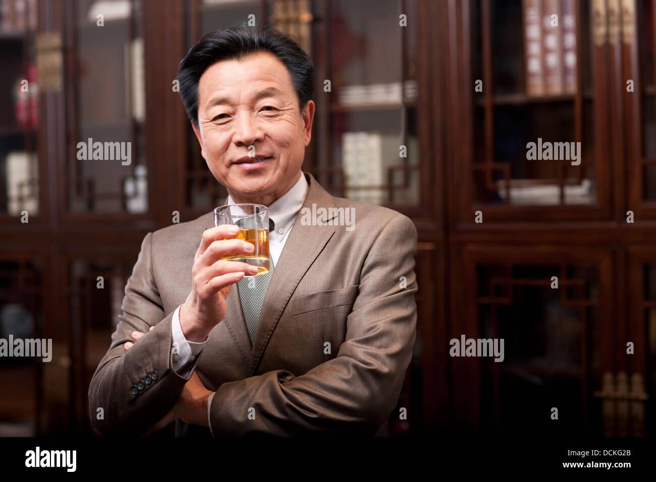 Successful businessman enjoying wine Stock Photo