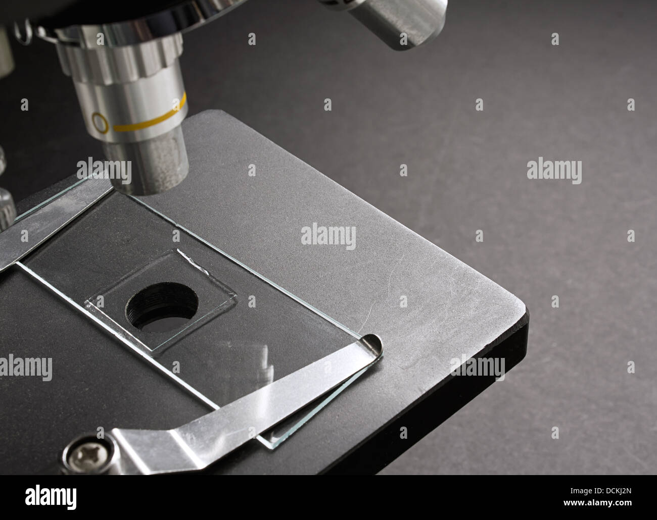 microscope with mounted glass slide on for microscopic inspection of cells - Stock Image