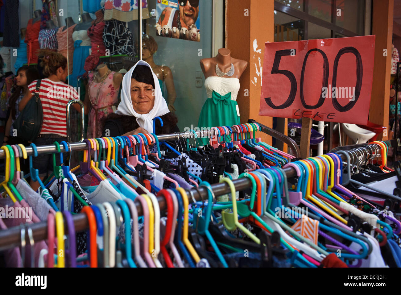 A woman shops for clothes in a clothing shop in Shkodra, Albania - Stock Image