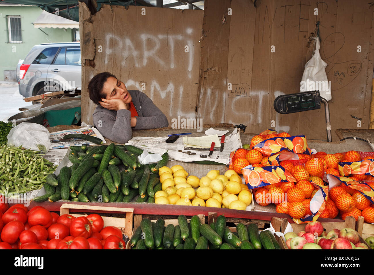 A vegetable and fruit seller sleeping at her stall in Tirana, Albania - Stock Image