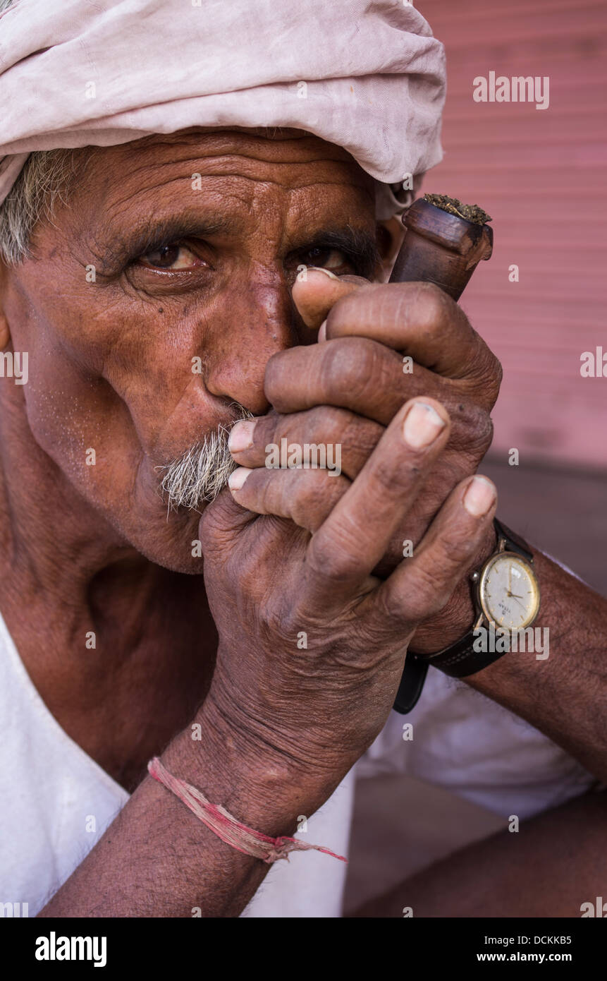 Indian man smoking tobacco with pipe - Jaipur, Rajasthan, India - Stock Image