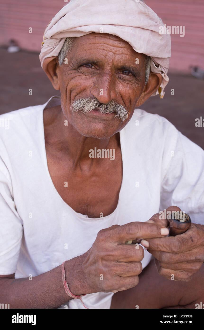 Indian man smoking tobacco with pipe - Jaipur, Rajasthan, India - Stock Image