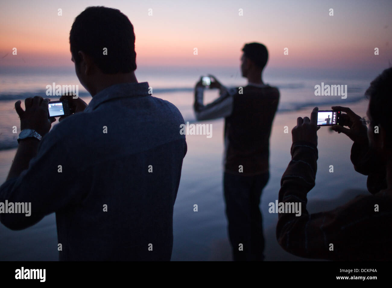 Bangladeshi tourists take photos of the sunset with their mobile phone cameras on the beach in Cox's Bazar, - Stock Image