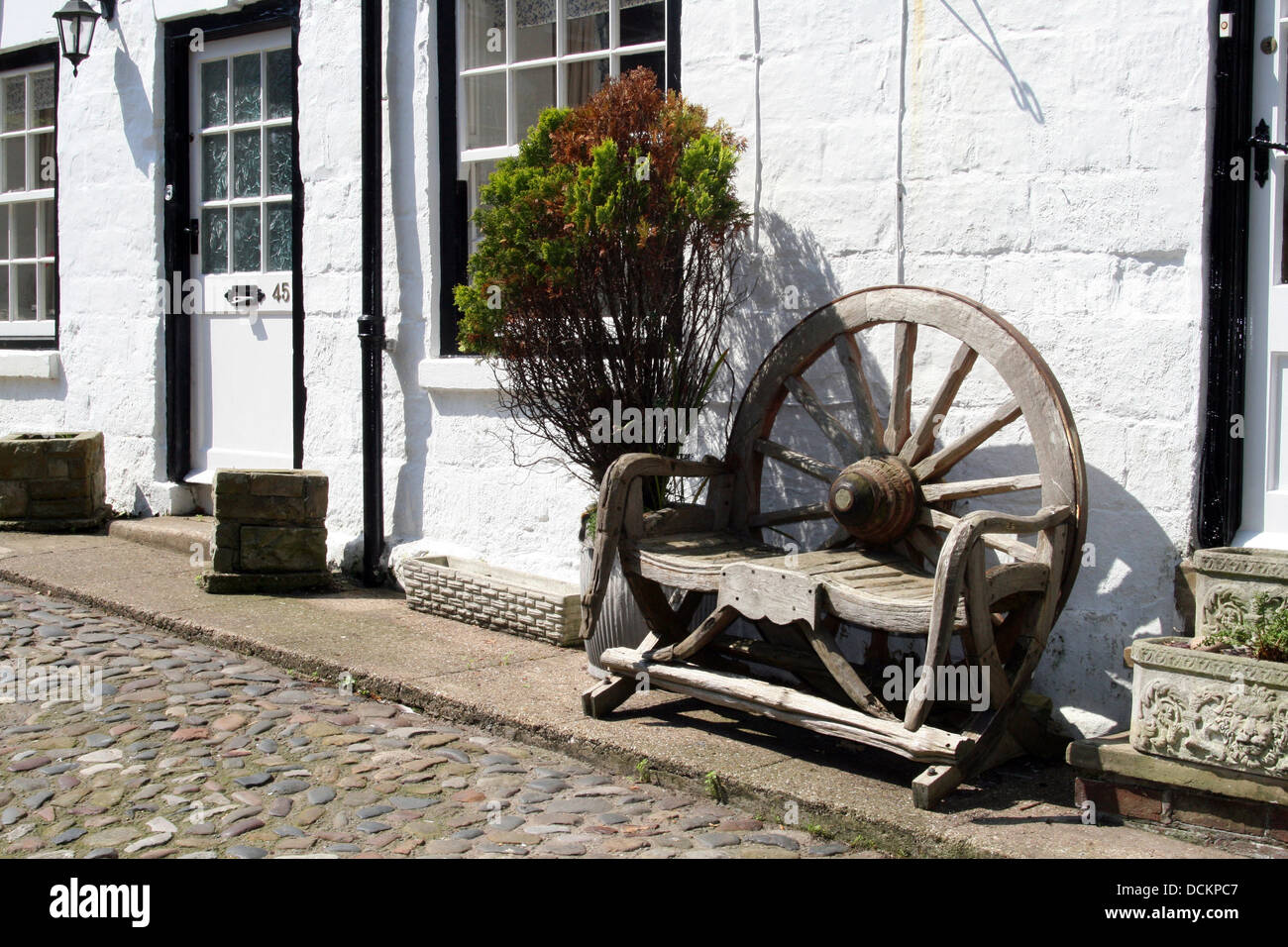 Old Cottage With Old Wooden Cartwheel Bench In The