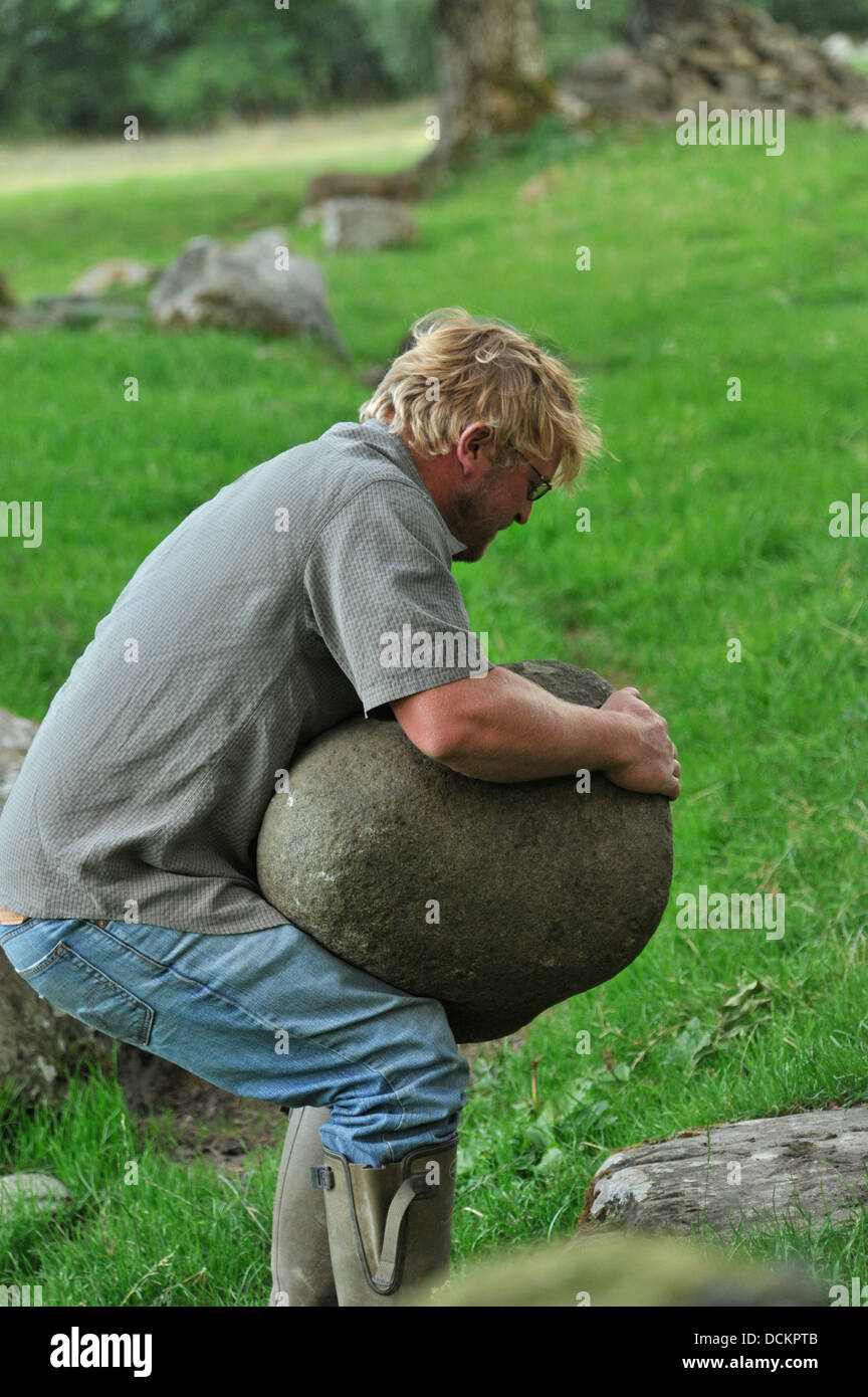 manhood stone being lifted in the scottish highlands - Stock Image