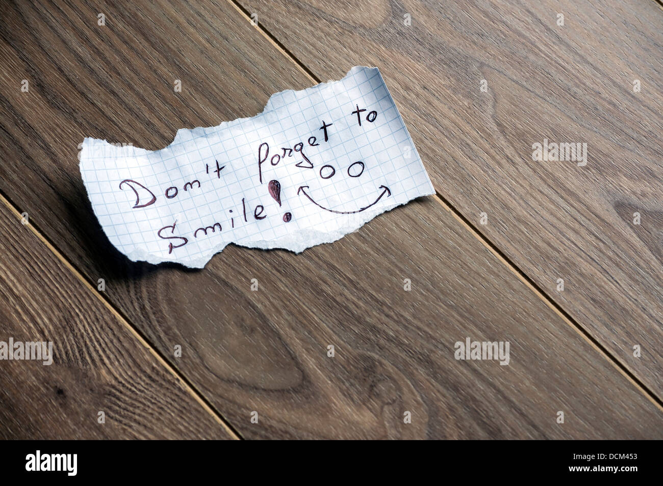 Don't forget to Smile - Hand writing text on a piece of paper on wood background with space for text - Stock Image