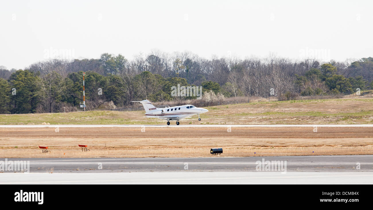 A Raytheon 390 private jet landing at a regional airport - Stock Image