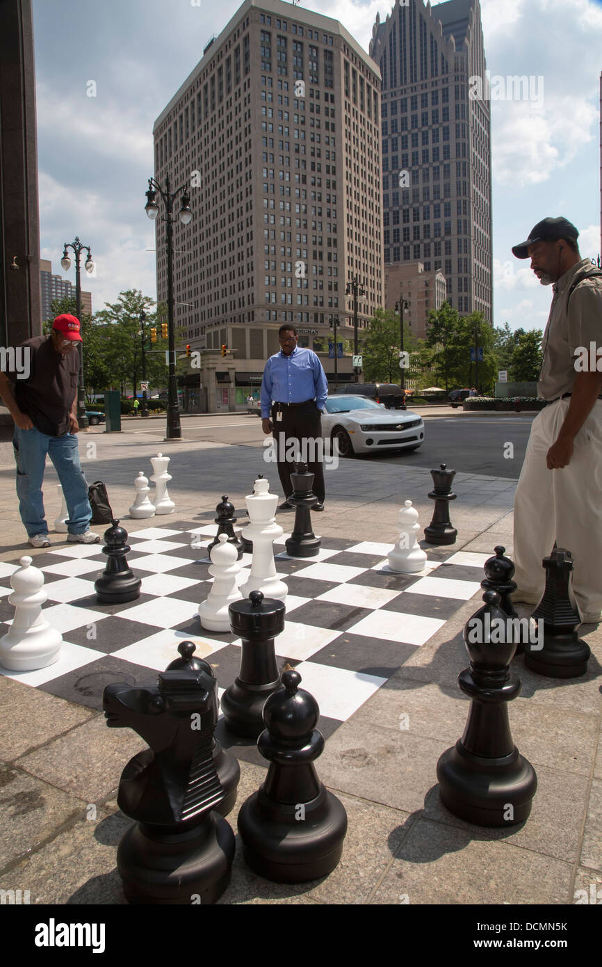 Detroit, Michigan - Two men play chess on a sidewalk chessboard in downtown Detroit as a third man watches. - Stock Image