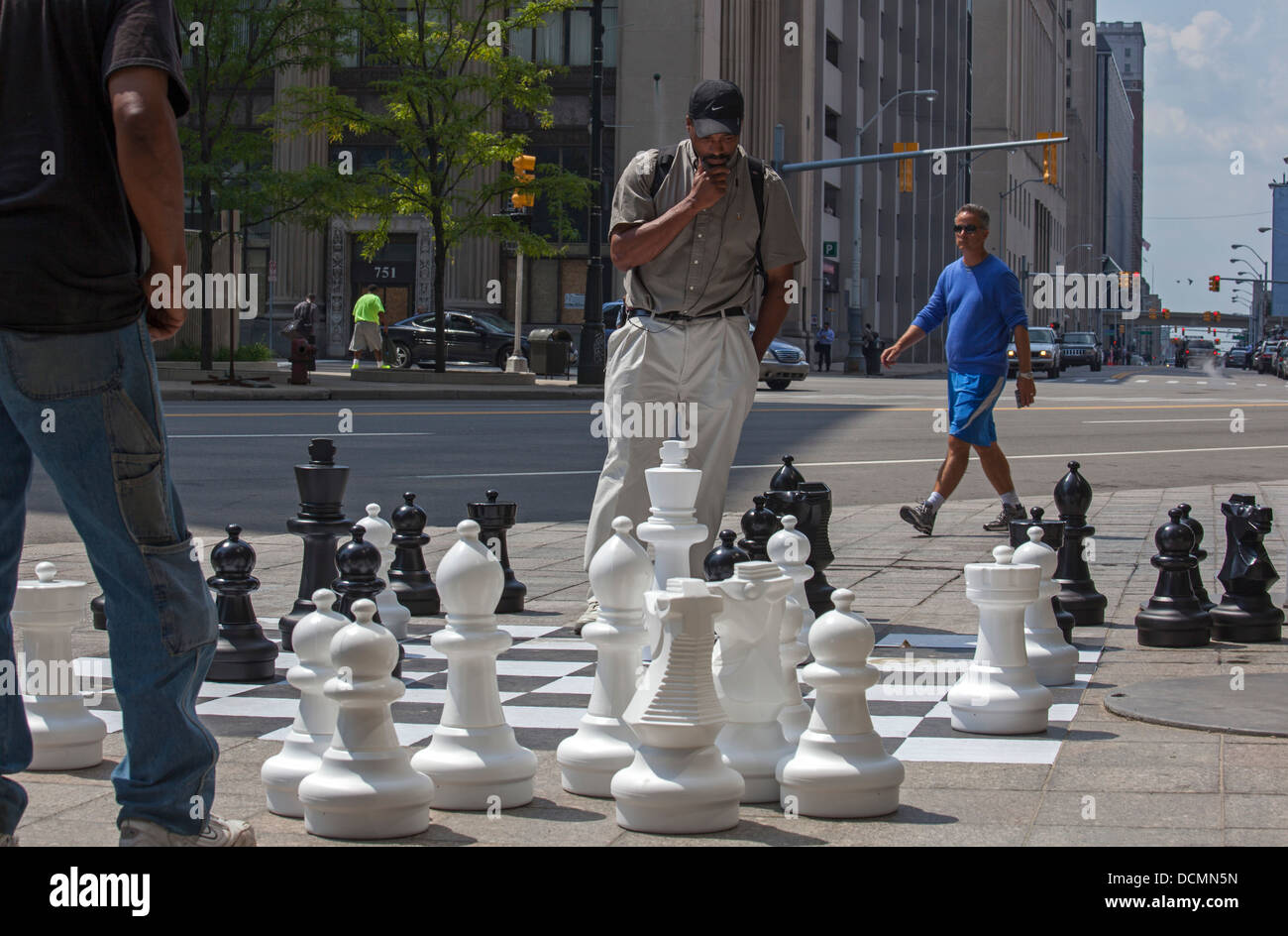 Detroit, Michigan - Two men play chess on a sidewalk chessboard in downtown Detroit. - Stock Image