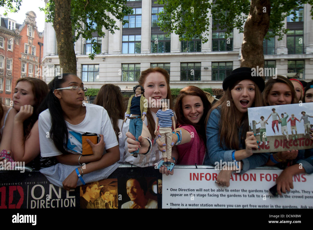 Leicester Square, London, UK. 20th August 2013.  Fans hold dolls of their favorite band members as thousands of - Stock Image
