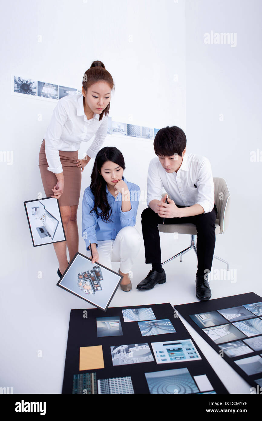 three interior designers working on a portfolio - Stock Image