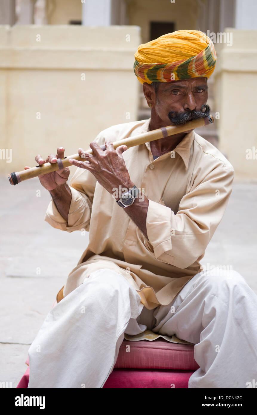 Man playing Bansuri traditional bamboo transverse flute at Meherangarh Fort - Jodhpur, Rajashtan, India - Stock Image