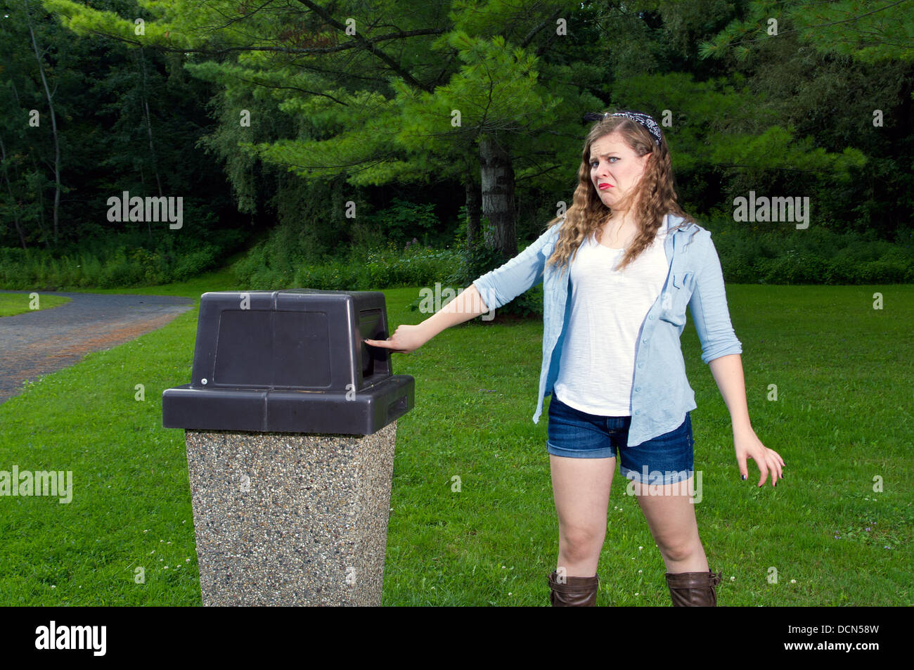 Teen Girl in a park looking in a trash can with a disgusting look on her face - Stock Image