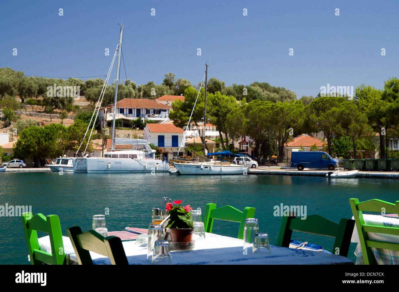 Yachts moored in Vathi Harbour from a waterfront Taverna, Meganisi, Lefkas, Ionian Islands, Greece. - Stock Image