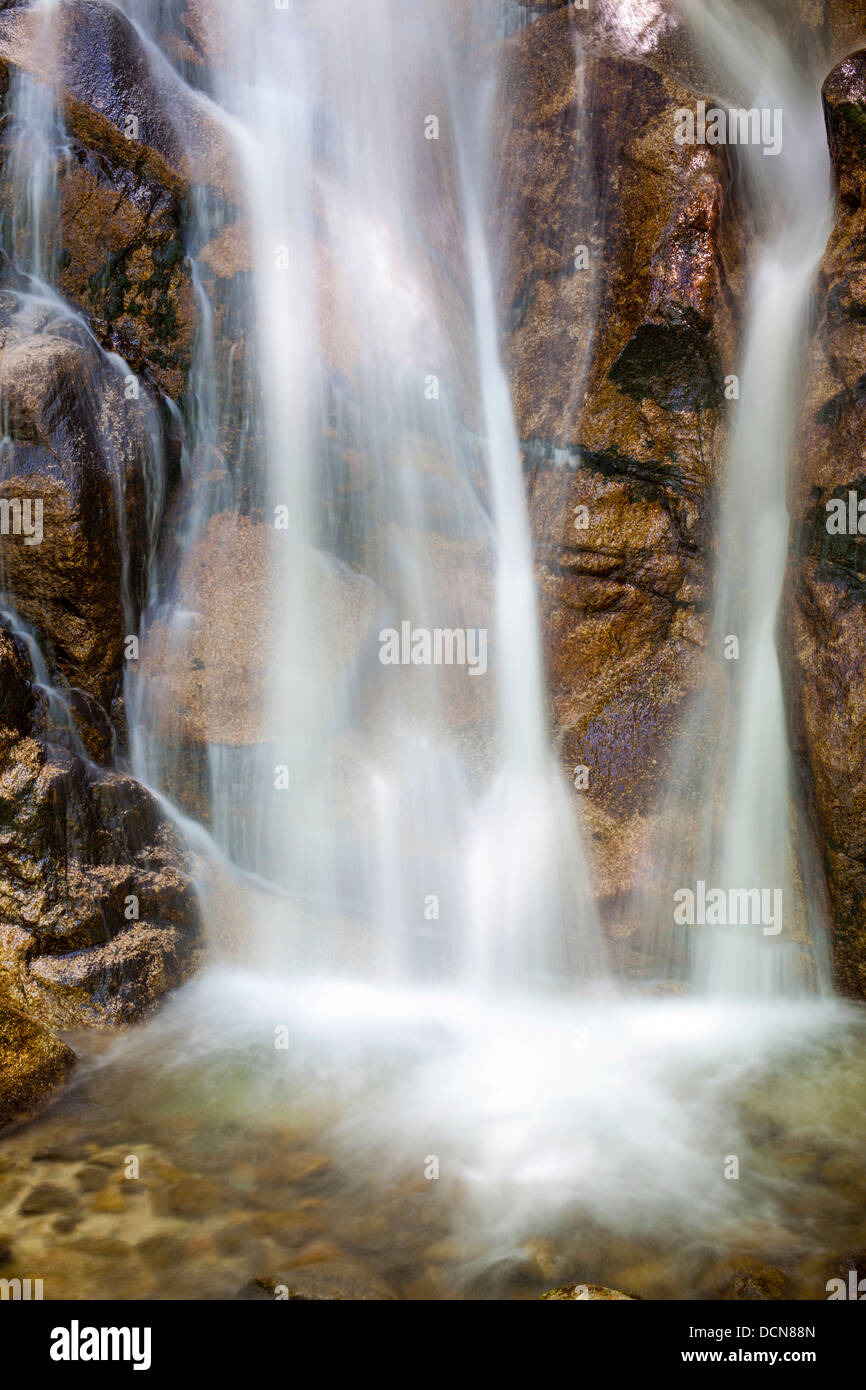 Close up of a waterfall and glistening rocks with long exposure blur. - Stock Image