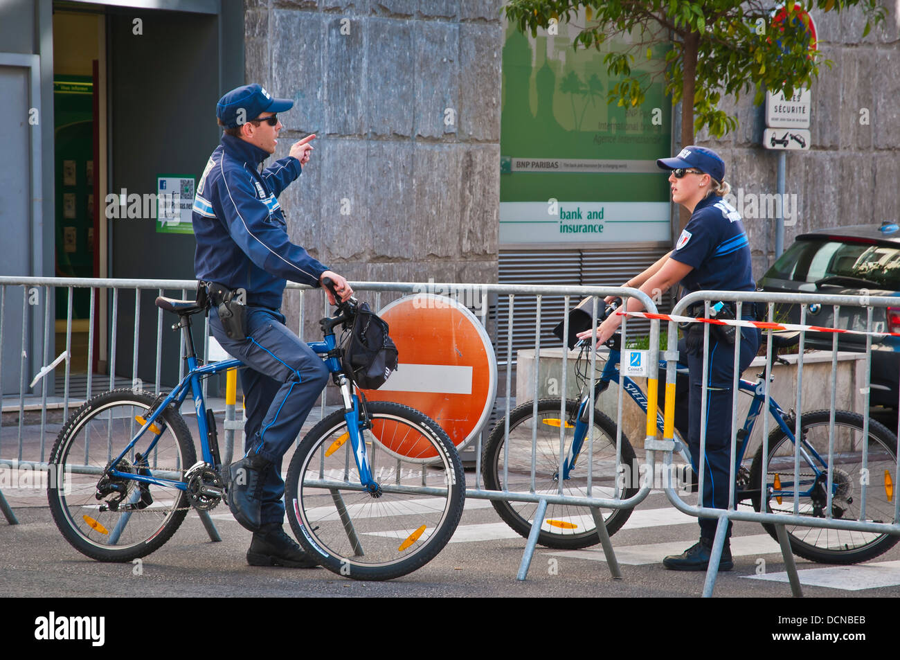 A street scene with two policemen conversations, Cannes, French Riviera, France. - Stock Image
