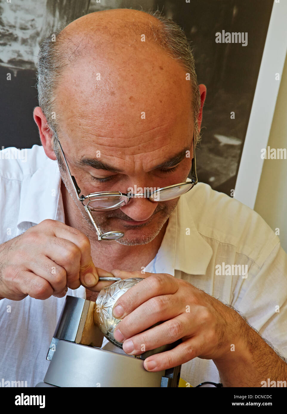 Silversmith inscribing a silver bowl with decorative marks - Stock Image