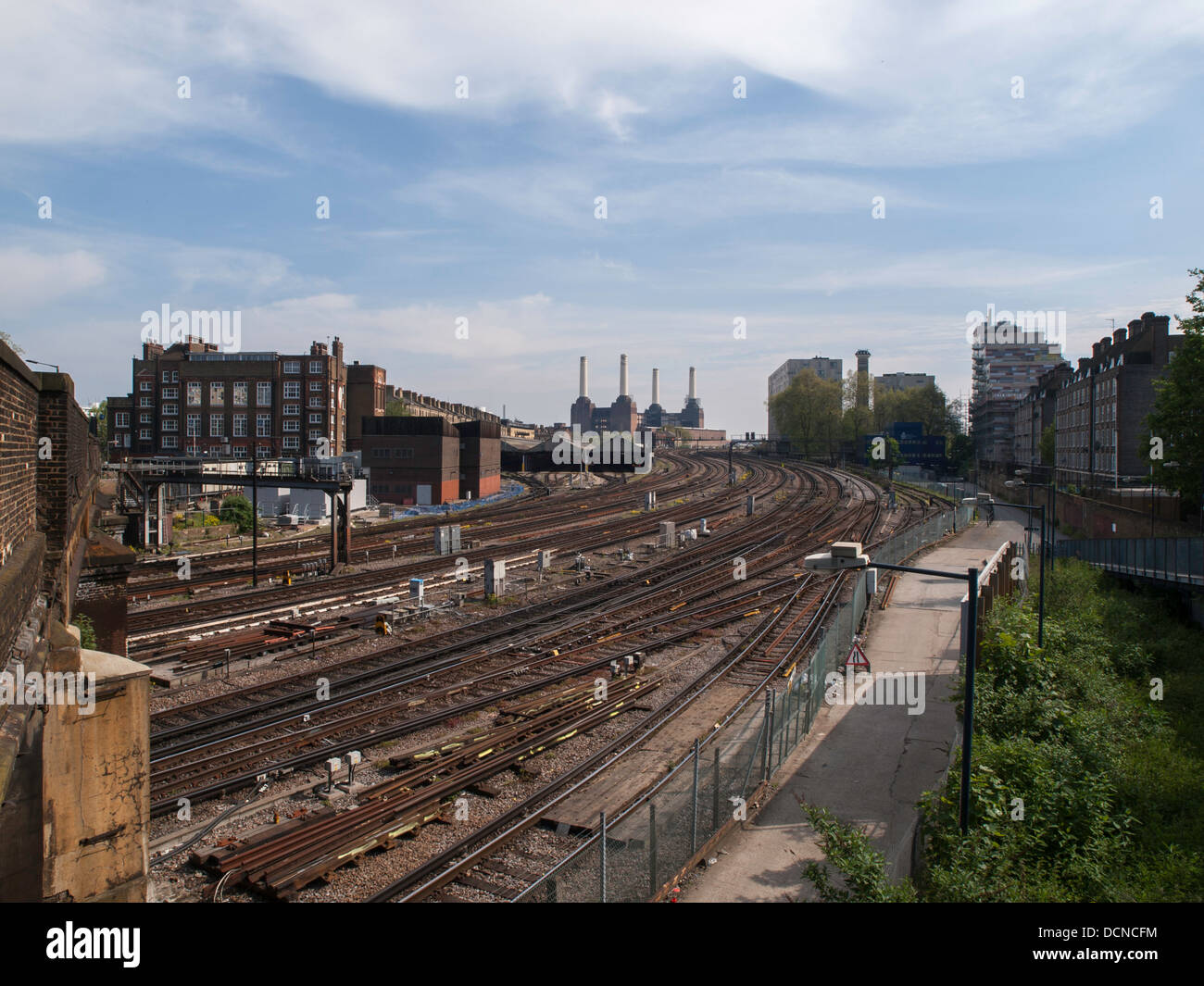 Battersea Power Station viewed from across the river beside busy railway lines. - Stock Image