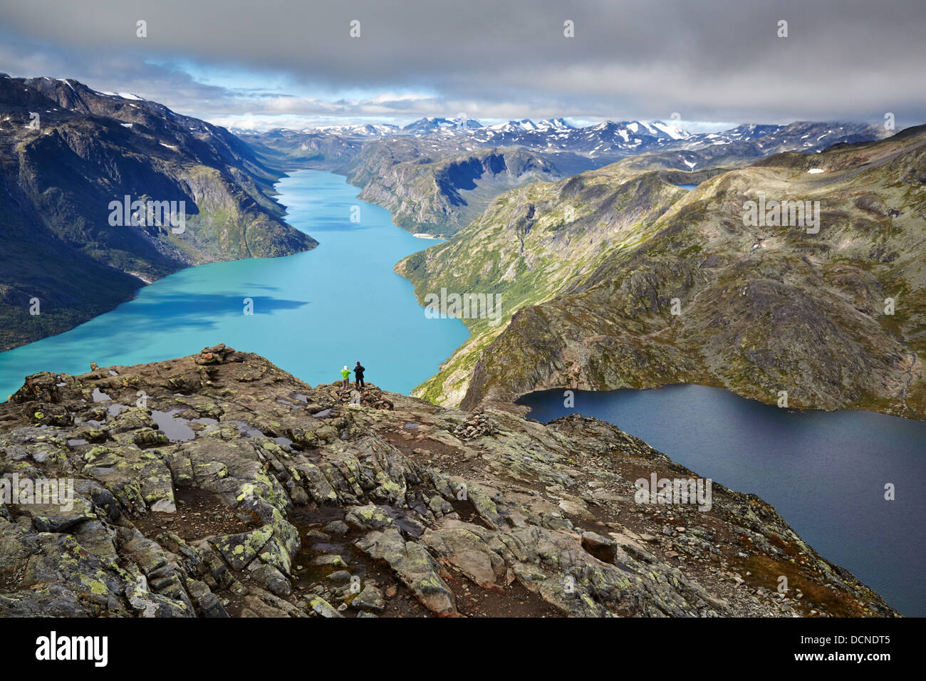 Two walkers look out over Lakes Gjende and Bessvatnet from the descent of the Besseggen Ridge Jotunheimen National - Stock Image