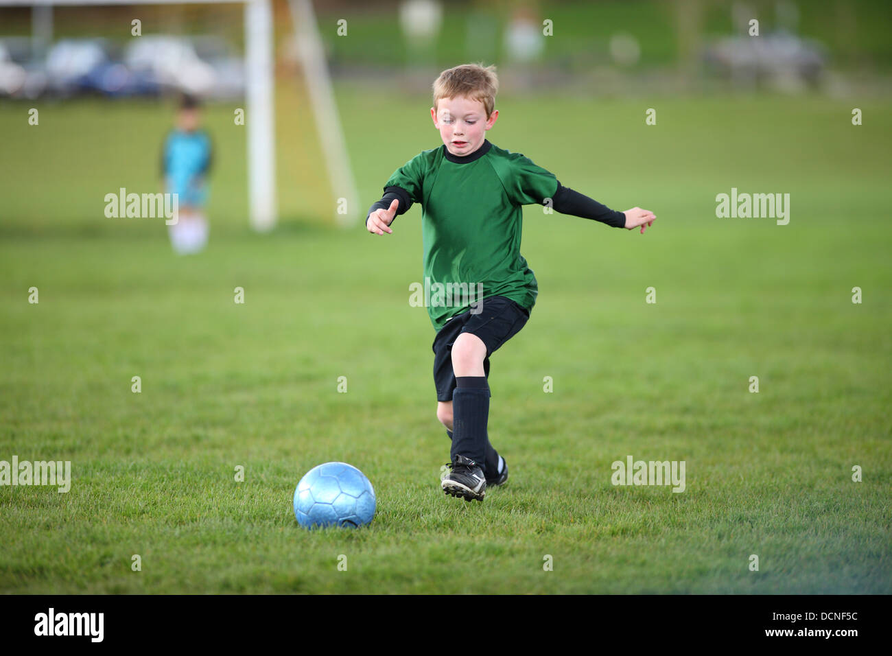Young boy kicking soccer ball - Stock Image