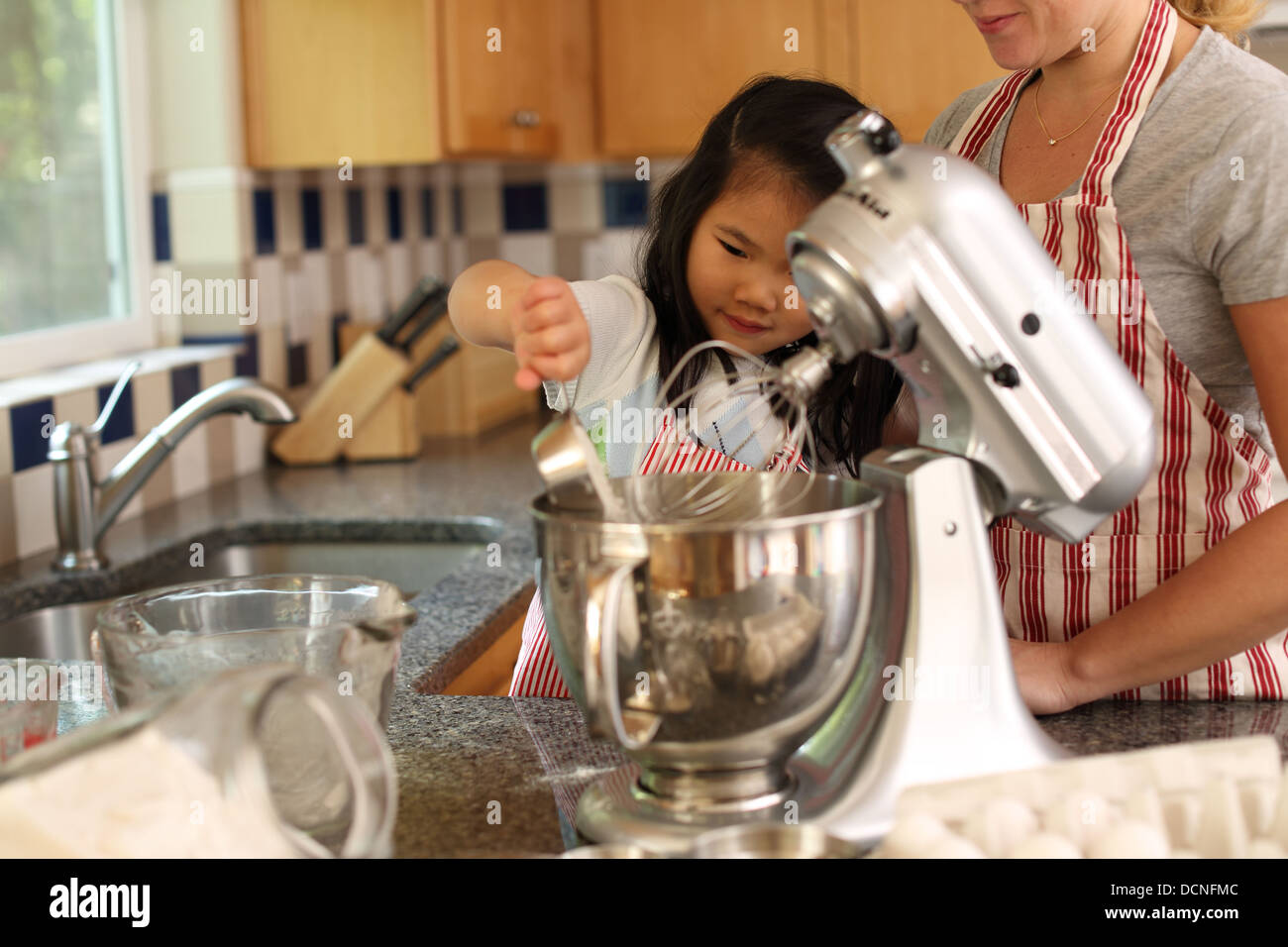 Young girl helping mother bake in kitchen - Stock Image