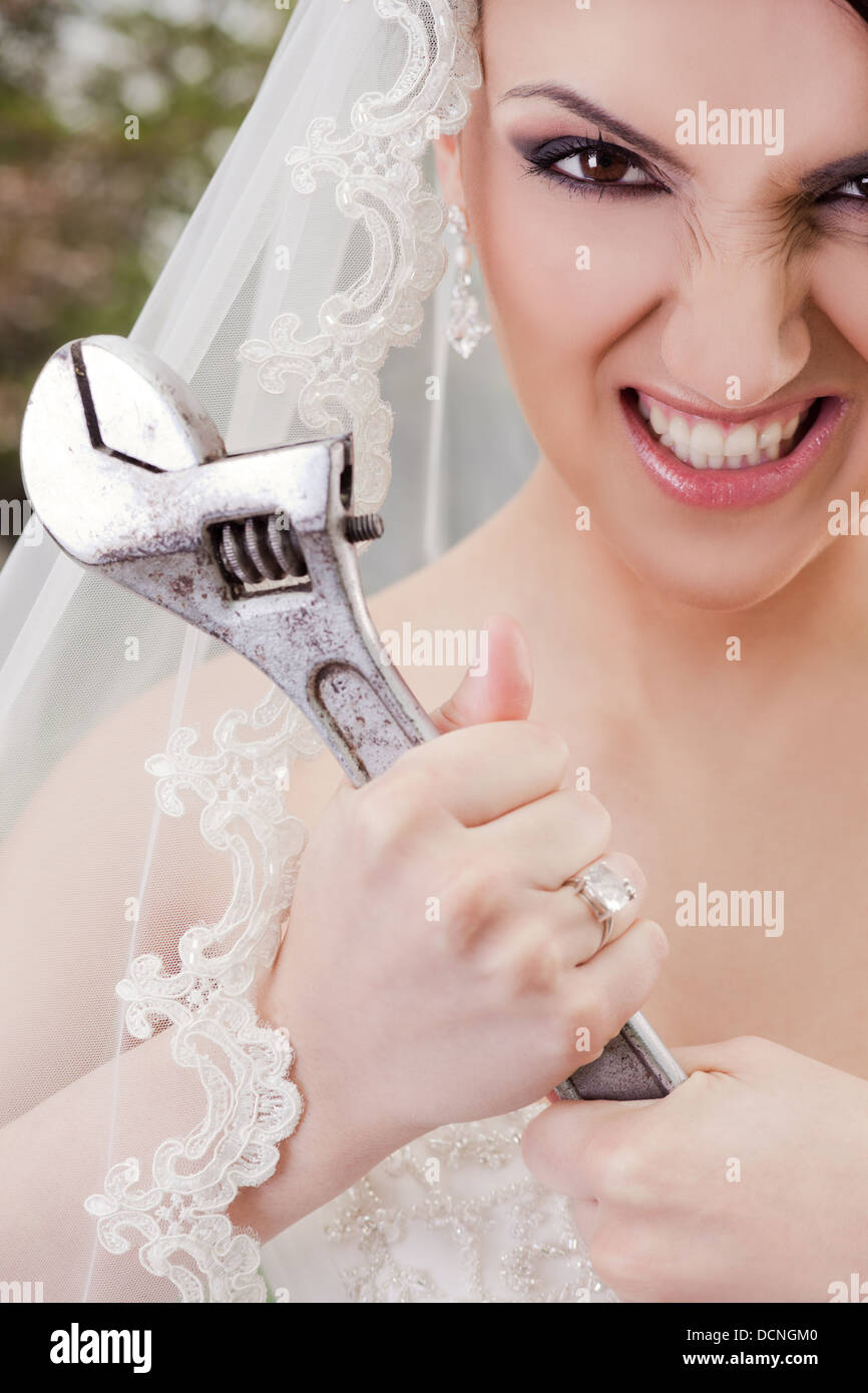 Furious bride holding wrench - Stock Image