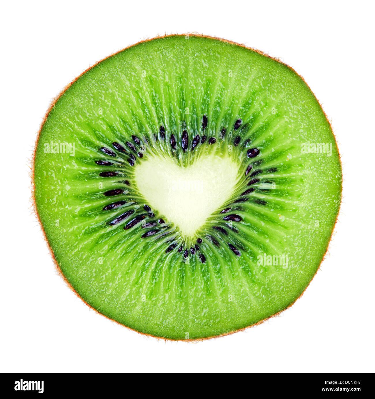 Sliced juicy kiwi fruit macro with heart shape over white. - Stock Image