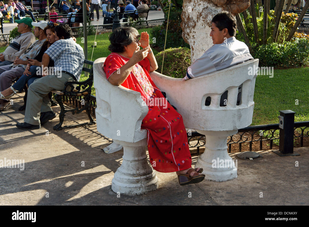 Elderly woman and younger man sitting and chatting in love seats in the main square of Merida, Yucatan, Mexico Stock Photo