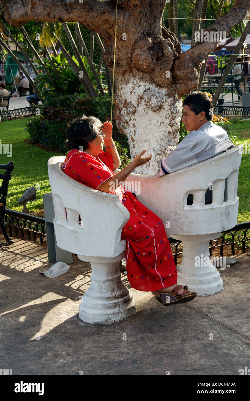 Elderly woman and younger man sitting and chatting in love seats in the main square of Merida, Yucatan, Mexico - Stock Image