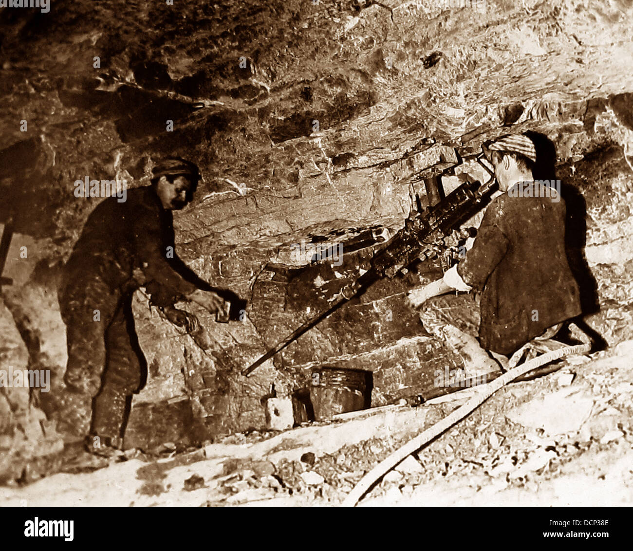 Coal miners drilling holes with a mechanised drill early 1900s - Stock Image