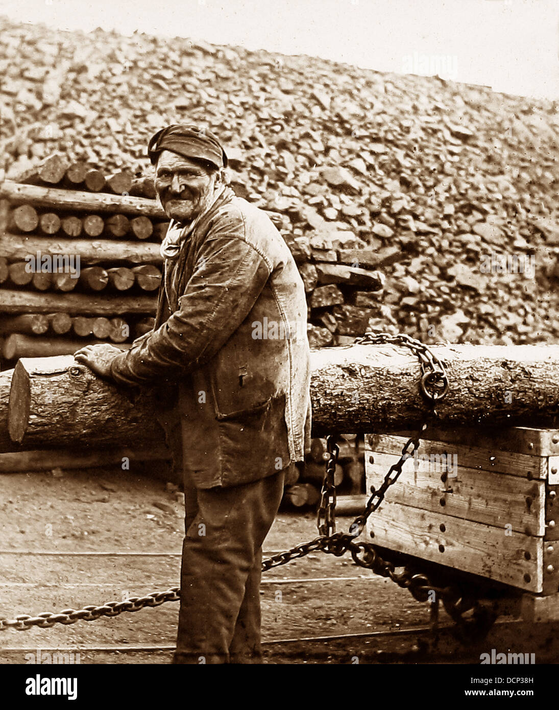 Taking a pit prop into the mine early 1900s - Stock Image