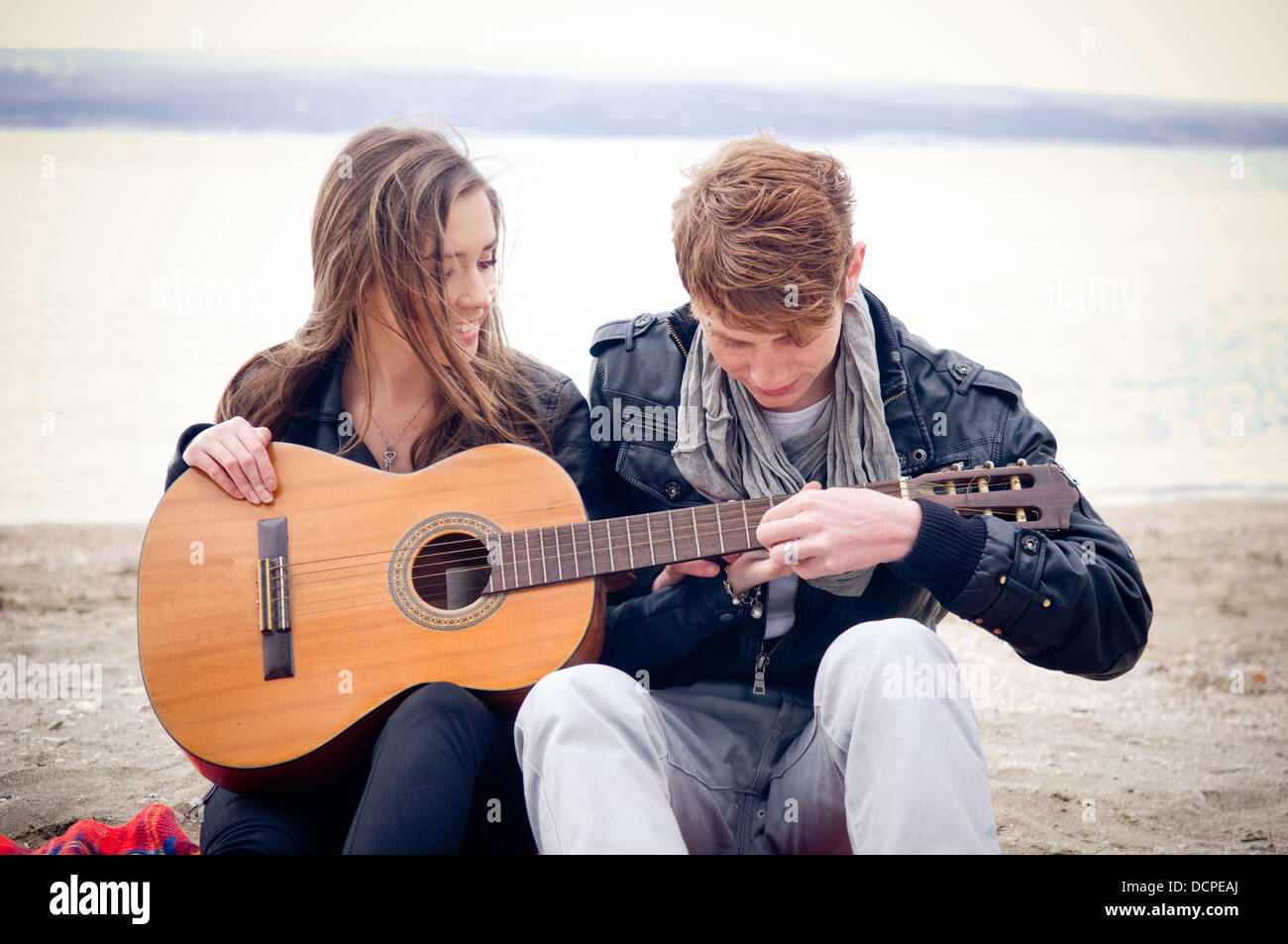 Young girl with acoustic guitar and her boyfriend on the bach - Stock Image