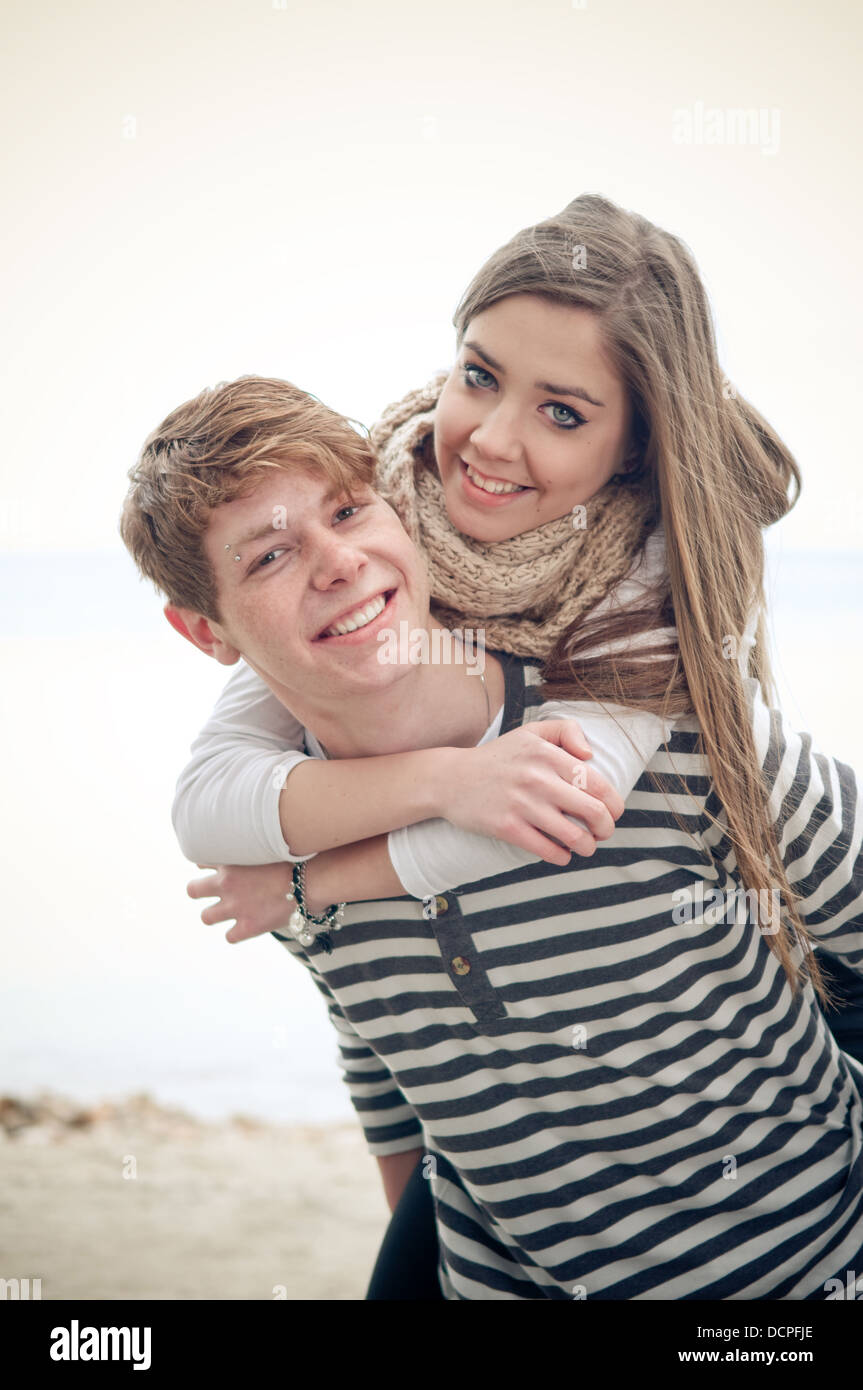 Teenage girl getting a piggyback from her boyfriend - Stock Image