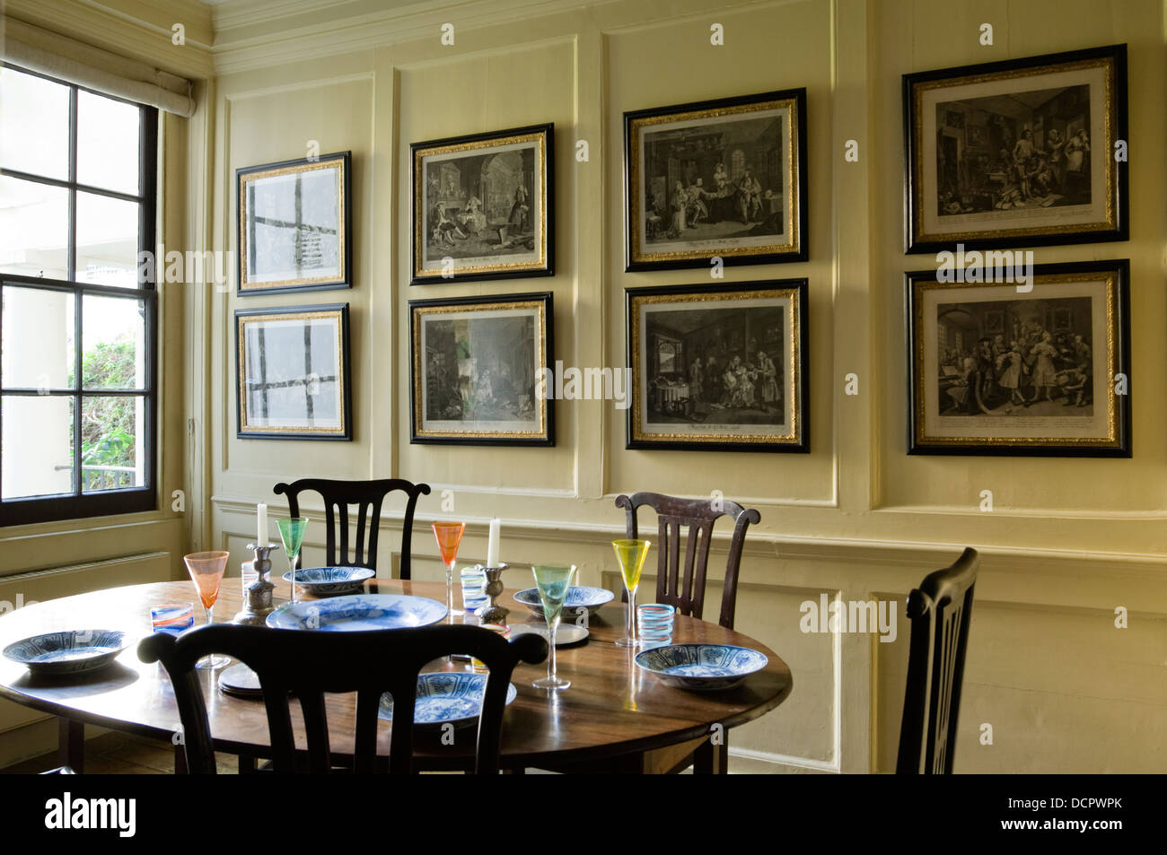 Venetian glassware on wooden table in dining room with collection of Hogarth's engravings on the wall Stock Photo